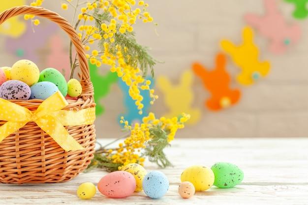 Uova di pasqua colorate in un cesto su un fondo di legno bianco, decorato con rametto di mimosa. concetto di vacanze di primavera.
