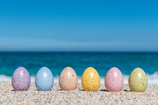 Uova di pasqua colorate sulla spiaggia in giornata di sole