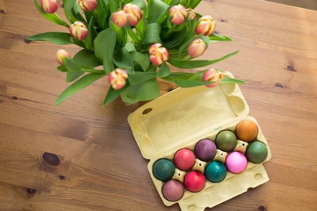 Uova di pasqua colorate nella casella su un tavolo