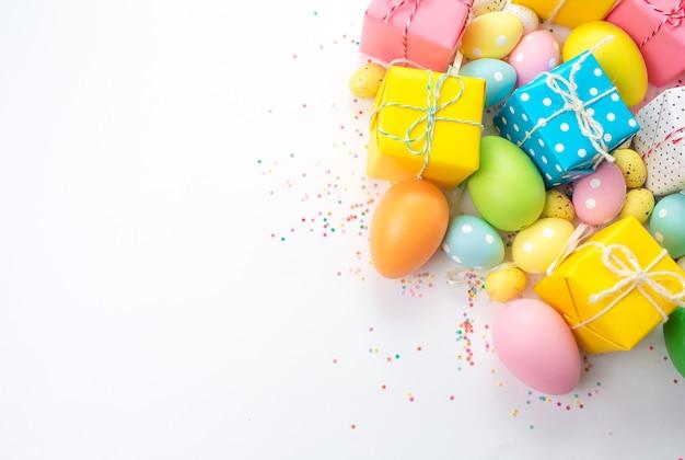 Le uova di pasqua colorate, le scatole con i regali sono su uno sfondo chiaro.