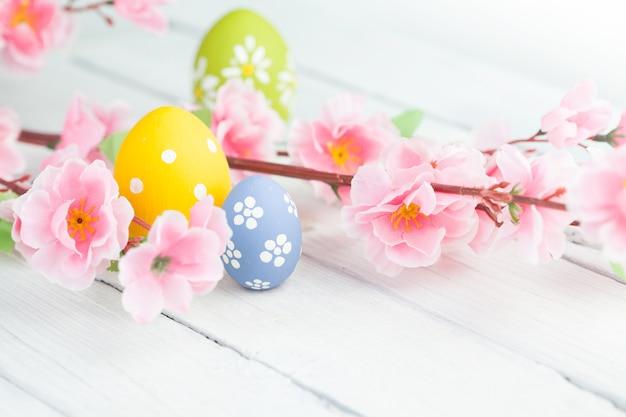 Uova di pasqua colorate e ramo con fiori