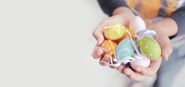 Uova di pasqua colorate nelle mani del bambino con copia spazio per testi, soft focus e tonalità di colore vintage.