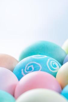 Uova di pasqua colorate tinte da acqua colorata isolate su uno sfondo blu pallido, concetto di design dell'attività delle vacanze di pasqua, primo piano, spazio copia.