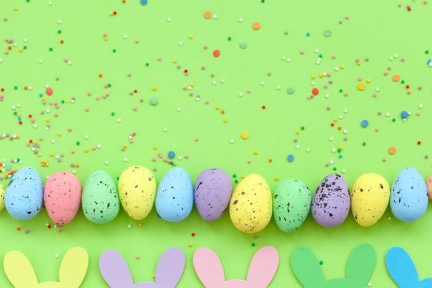 Uova di pasqua colorate e ghirlanda di pasqua coniglietto fatto a mano su sfondo verde. vista dall'alto, piatto. felice pasqua concetto.