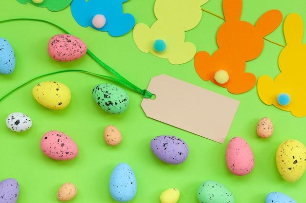 Uova di pasqua colorate e ghirlanda di pasqua coniglietto fatto a mano con etichetta vuota su sfondo verde. vista dall'alto, piatto. felice pasqua concetto.