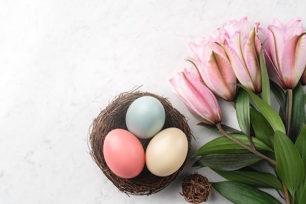 Uova di pasqua colorate nel nido con fiori di giglio rosa sul fondo della tavola in marmo bianco brillante.