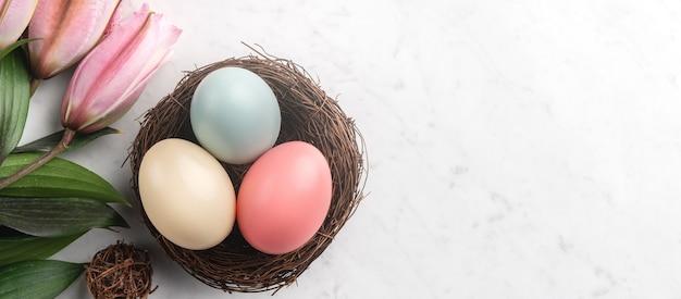 Uova di pasqua colorate nel nido con fiori di giglio rosa sulla superficie del tavolo in marmo bianco brillante.