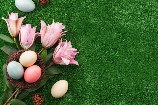Uova di pasqua colorate nel nido con fiori di giglio rosa su una superficie di erba del prato.