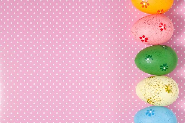 Uova di pasqua colorate su sfondo a pois. vista dall'alto, piatto con spazio per il testo. sfondo di pasqua, banner.