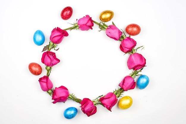 Uova di pasqua colorate e fiori di rosa a forma di cerchio su sfondo bianco