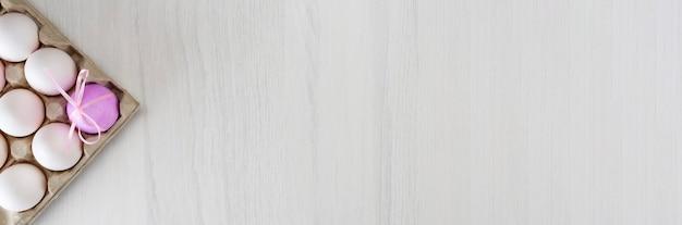 Uova di pasqua colorate su un supporto su un tavolo grigio con posto per testo, vista dall'alto, banner