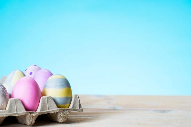 Uova di pasqua colorate su un supporto su un tavolo su una superficie blu