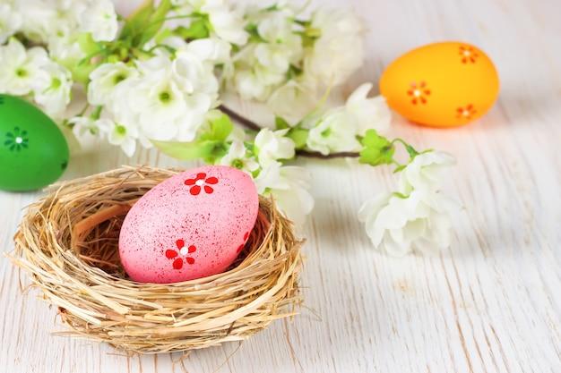 Uova di pasqua colorate nel nido di paglia e ramo con fiori su fondo di legno bianco con spazio per testo.