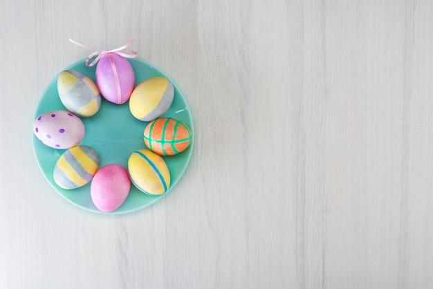 Uova di pasqua colorate su una piastra turchese su un tavolo grigio con posto per testo, vista dall'alto