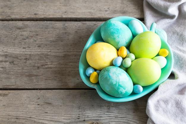 Uova di pasqua colorate in un piatto turchese su uno sfondo di legno squallido