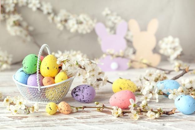 Uova di pasqua colorate in un cesto bianco decorato con primavera sbocciano i fiori di ciliegio