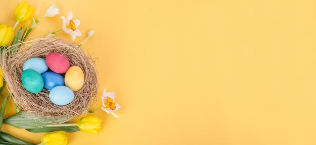 Uova di pasqua colorate con un bouquet di tulipani gialli e narcisi su uno sfondo giallo, con spazio di copia