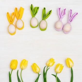 Uova di pasqua colorate con orecchie di stoffa come coniglietto di pasqua. tulipano di fiori di primavera giallo brillante