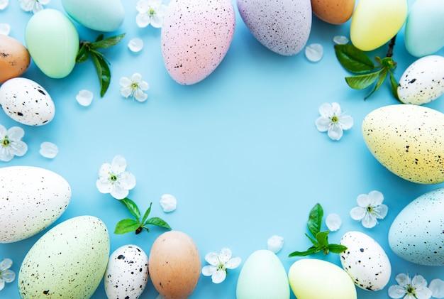 Uova di pasqua colorate con fiori di primavera sbocciano i fiori su sfondo blu.