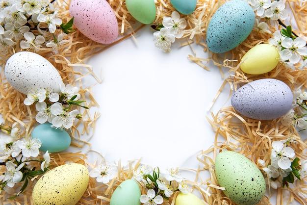 Uova di pasqua colorate con fiori di primavera sbocciano i fiori isolati su sfondo bianco.