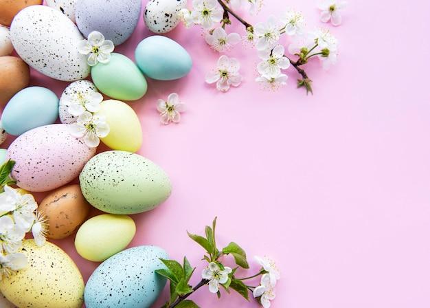 Uova di pasqua colorate con fiori di primavera sbocciano i fiori su sfondo rosa.