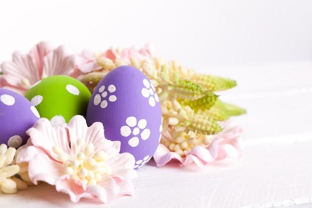 Uova di pasqua colorate con punti bianchi nel nido di paglia