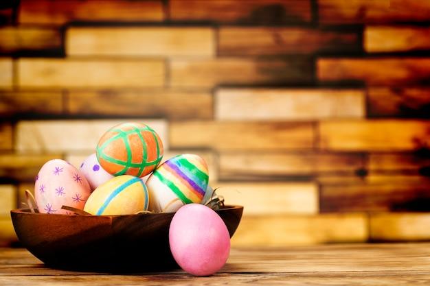 Uova di pasqua colorate sul piatto di legno sul tavolo