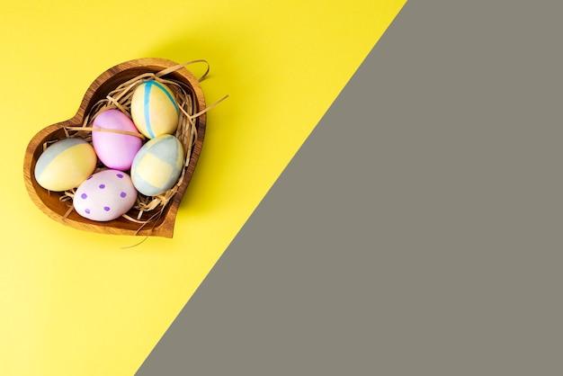 Uova di pasqua colorate in un piatto di legno su una superficie gialla e grigia