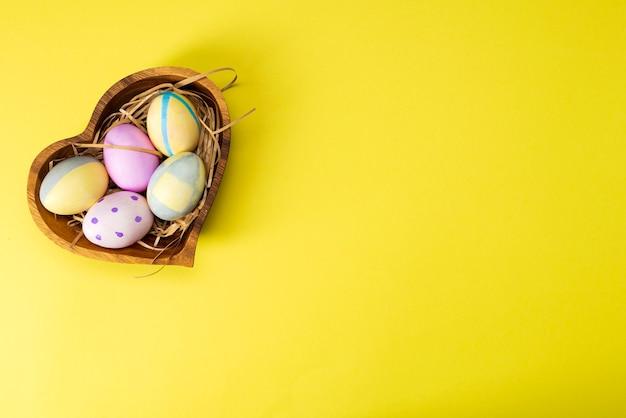 Uova di pasqua colorate nel piatto di legno sulla superficie gialla