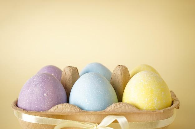 Uova di pasqua colorate su superficie gialla, primo piano, posto per il testo.