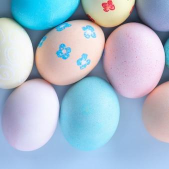 Uova di caccia di pasqua colorate tinte da acqua colorata con bellissimo motivo su sfondo blu pastello, concetto di design di vacanza, vista dall'alto, copia dello spazio.