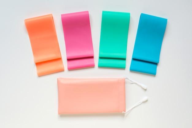 Fasce elastiche colorate per il fitness e custodia su sfondo bianco strumenti per attrezzature sportive o per il fitness