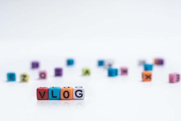 Cubo variopinto di alfabeto inglese con la parola vlog su libro bianco