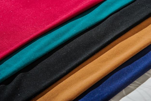 Campioni di tessuto colorato su tavola di legno e sfondo sfocato chiaro