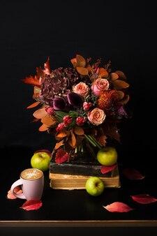 Bouquet colorato autunno. composizione autunnale con cappuccino caldo, libri, rose, tulipani, foglie secche ed erbe aromatiche.