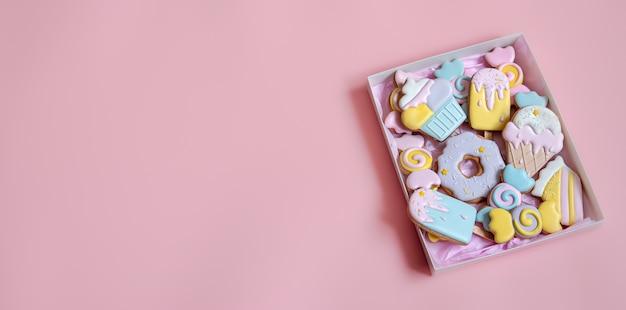 Biscotti di pan di zenzero festivi colorati di diverse forme ricoperti di glassa su sfondo rosa spazio copia.