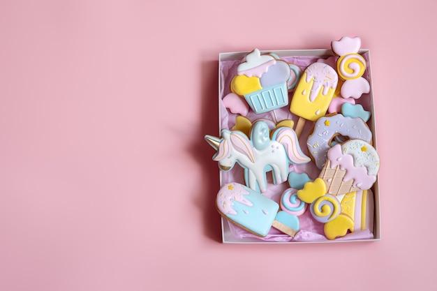 Biscotti di pan di zenzero festivi colorati di diverse forme ricoperti di glassa su sfondo rosa spazio copia