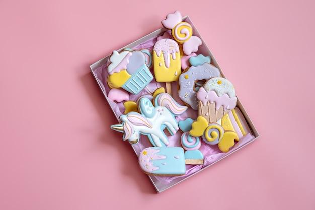Biscotti di pan di zenzero festivi colorati di diverse forme ricoperti di glassa su sfondo rosa.