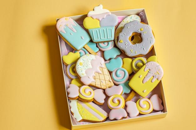 Biscotti di pan di zenzero festivi colorati di diverse forme ricoperti di glassa.