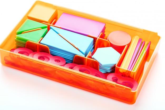 Figure colorate e numeri per bambini in una scatola. uno strumento per sviluppare il pensiero dei bambini.