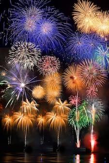 Fuochi d'artificio colorati. i fuochi d'artificio sono una classe di dispositivi pirotecnici esplosivi utilizzati per scopi estetici e di intrattenimento. rumore visibile dovuto a scarsa illuminazione, messa a fuoco morbida, dof poco profondo, leggera sfocatura del movimento
