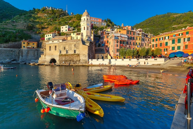 Le colorate barche da pesca e la chiesa di santa margherita di antiochia nel porto di vernazza nelle cinque terre, il parco nazionale delle cinque terre, liguria, italia.