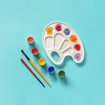 Fiori colorati su tavolozza artistica, pennello, tempera su sfondo blu, spazio per copie. colori estivi concept creativo o giornata internazionale dei fiori. vista dall'alto modello piatto per invito a cartolina.