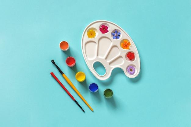 Fiori colorati su tavolozza artistica, pennello, tempera