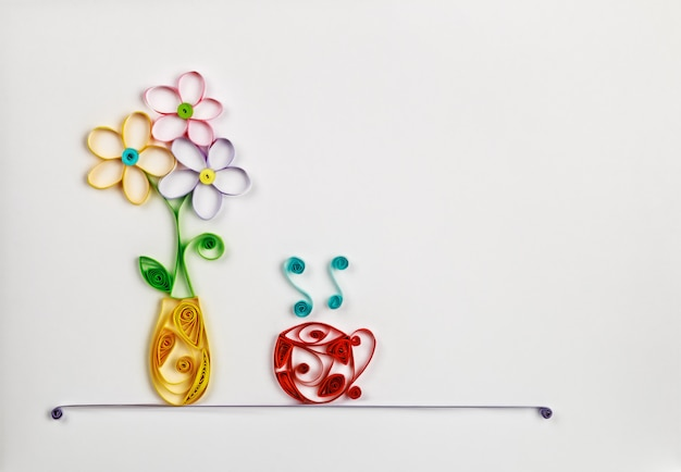 Fiori colorati in un vaso e una tazza calda fatta di quilling