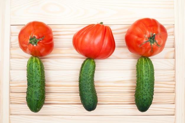 Fiori variopinti su un fondo di legno fatto con i pomodori e i cetrioli. concetto di cibo sano.