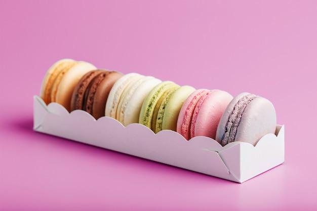 Biscotti colorati macarons francesi in un pacchetto su una superficie rosa. primo piano, spazio libero