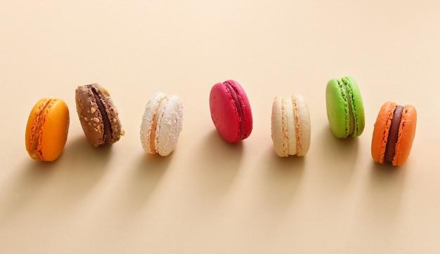 Amaretti francesi colorati su fondo beige. biscotti alle mandorle vista dall'alto, piatto. concetto di regalo dolce di san valentino, vacanza, celebrazione.