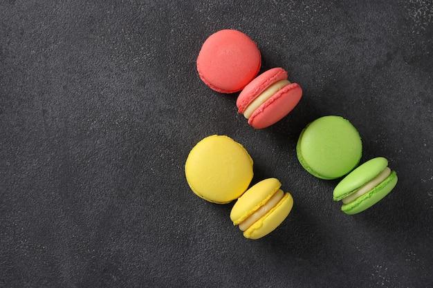 Amaretti francesi colorati su sfondo grigio scuro. vista dall'alto. formato orizzontale