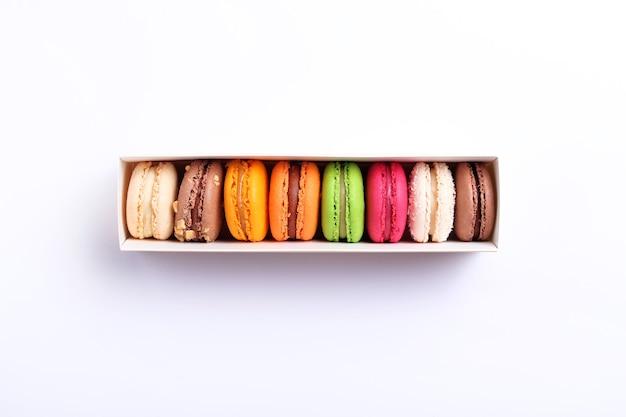 Colorati amaretti francesi in confezione regalo su sfondo bianco. biscotti alle mandorle vista dall'alto, piatto. concetto di regalo dolce di san valentino, vacanza, celebrazione.